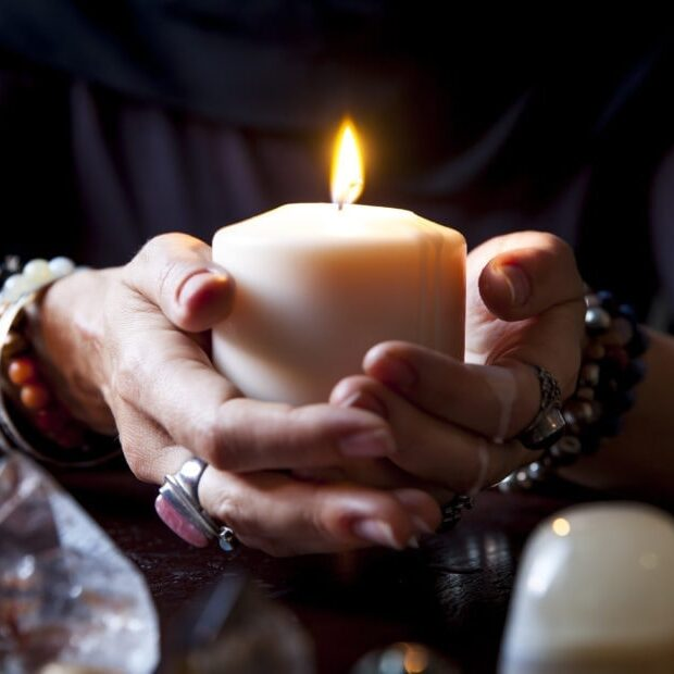 female hands holding a burning candle