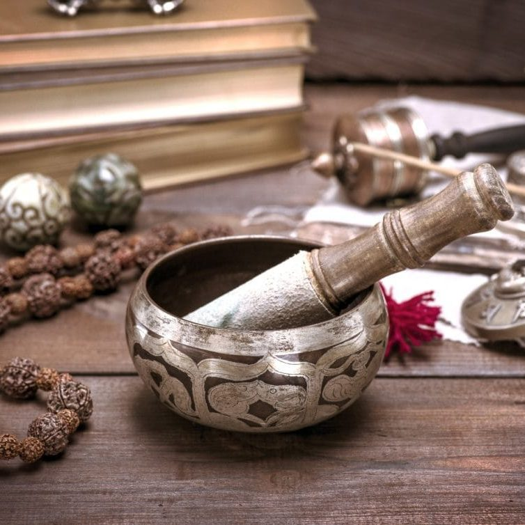 a copper singing bowl and a wooden stick on a brown table, next to a rosary